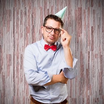 Man wearing a red bow tie and party hat. In a deep reflexion.