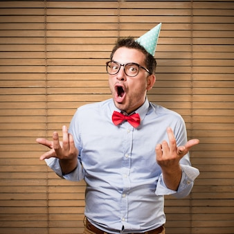 Man wearing a red bow tie and party hat. Looking funny.