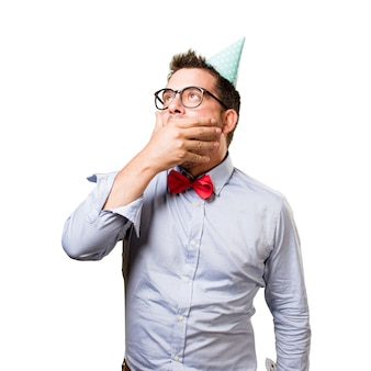 Man wearing a red bow tie and party hat. Looking surprised.