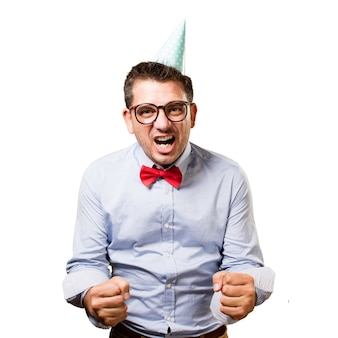 Man wearing a red bow tie and party hat. Looking upset.