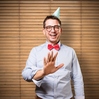 Man wearing a red bow tie and party hat. Smiling.