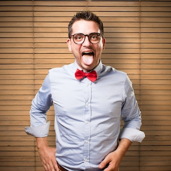 Man wearing a red bow tie. Pulling his tongue out.
