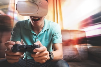 Man wearing virtual reality goggles watching movies or playing video games. The vr headset design is generic and no logos.