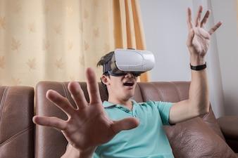 仮想現実を身につけている男が映画を見たり、ビデオゲームをしたりします。 vrヘッドセットのデザインは一般的でロゴはありません。
