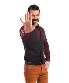 Man wearing waistcoat counting five