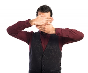 Man wearing waistcoat covering his face