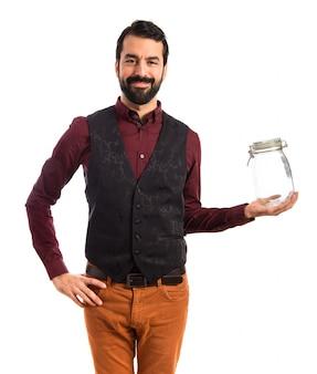 Man wearing waistcoat holding an empty glass jar