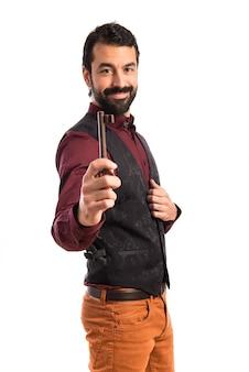 Man wearing waistcoat holding vintage key