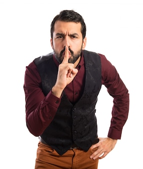 Man wearing waistcoat making silence gesture