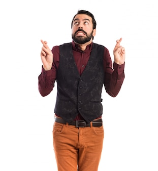 Man wearing waistcoat with his fingers crossing