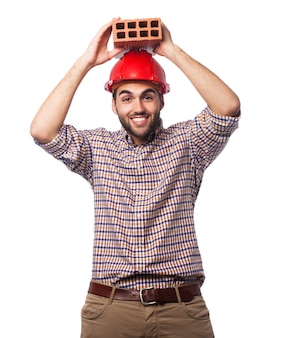 彼の頭の上に赤いヘルメットとレンガを持つ男