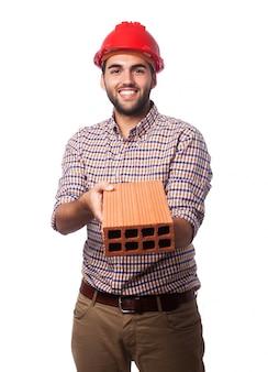 赤のヘルメットとレンガを持つ男