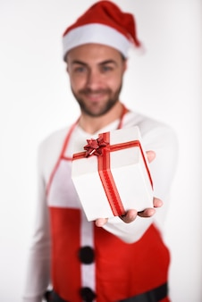 Man with beard wearing santa claus clothes with a gift box