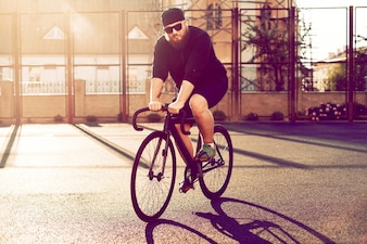Man with black cap riding bicycle