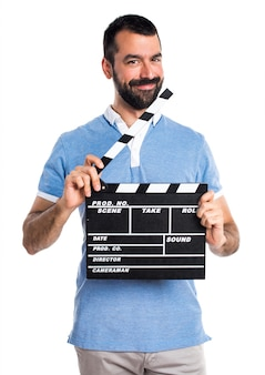 Man with blue shirt holding a clapperboard
