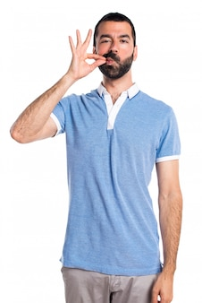 Man with blue shirt making silence gesture