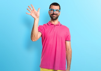 Man with colorful clothes saluting on colorful background