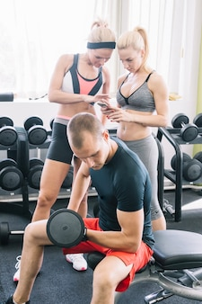 Man with dumbbell and women with smartphone