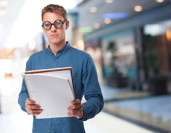 Man with glasses looking at a notepad