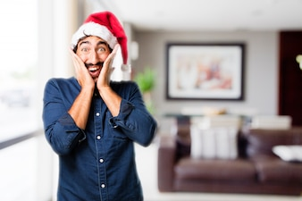 Man with hands on face and santa hat