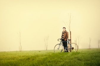 Man with his bike on a foggy day