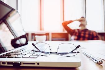 Человек с его рукой, удерживая его лицо, тормозит от работы с ноутбуком и ноутбуком с очками на деревянном столе. концепция стресса / отдыха / напряжения / неудачи / обескуражения / депрессии
