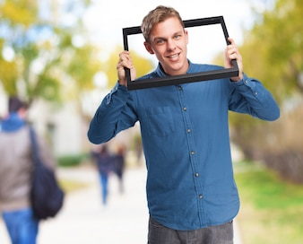 Man with his head stuck in a black frame