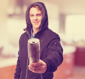 Man with hood of hoodie put on holding a can