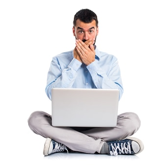 Man with laptop covering his mouth