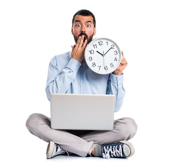 Man with laptop holding a watch