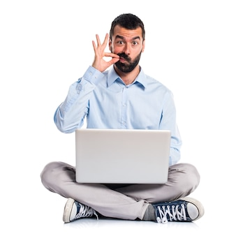 Man with laptop making silence gesture