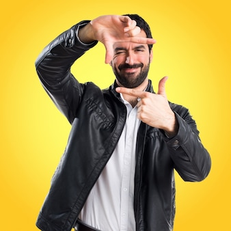 カラフルな背景に彼の指で焦点を合わせる革ジャケットを持つ男