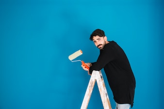 Man with paint roll on ladder