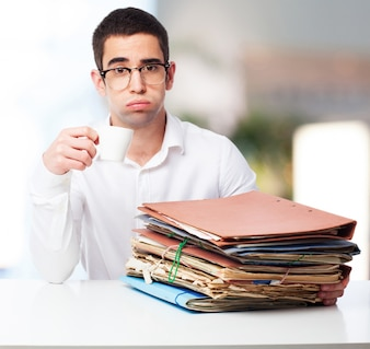 Man with pitying face with a mountain of folders and a coffee