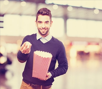 Man with popcorn in one hand and a package in the other