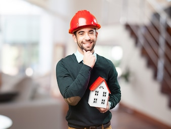 Man with red helmet and a small house in hand