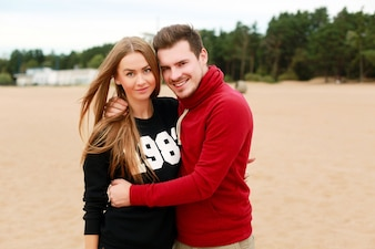 Man with red sweatshirt hugging his girlfriend on the beach