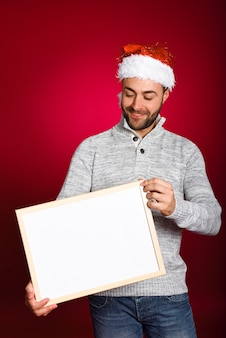 Man with santa hat holding blank board
