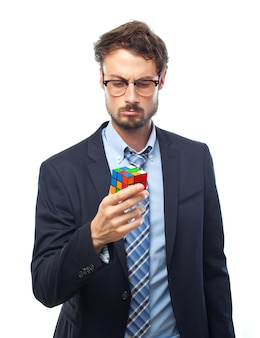 Man with suit looking at a cube of rubik