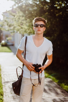 Man with sunglasses with a reflex camera in hands