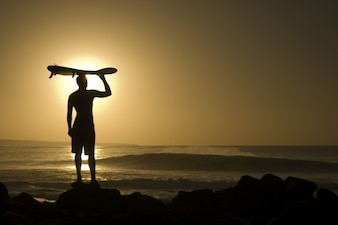 Man with surfboard looking at the sunset
