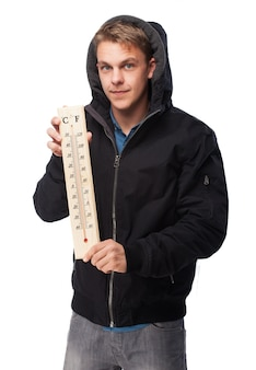 Man with sweatshirt holding a thermometer