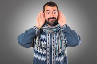 Человек с зимней одеждой, слушать что-то на сером фоне
