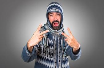 Человек с зимней одежды, делая жест победы на сером фоне