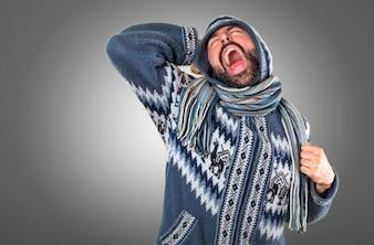 Человек с зимней одеждой, зевая на сером фоне