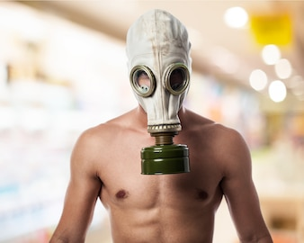 Man without a shirt with a gas mask