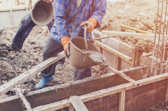 Man worker mixing cement mortar plaster for construction with vintage tone.