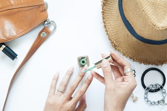Manicure process. Nail polish being applied to hand, polish is a green color. Woman accessories on white background