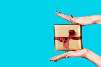Manos sujetando tres regalos en un fondo azul