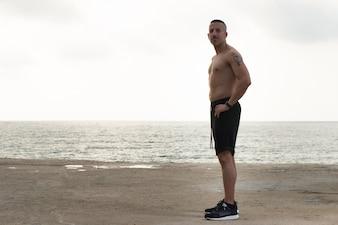 Мужественный красивый молодой человек, отдыхая на пляже